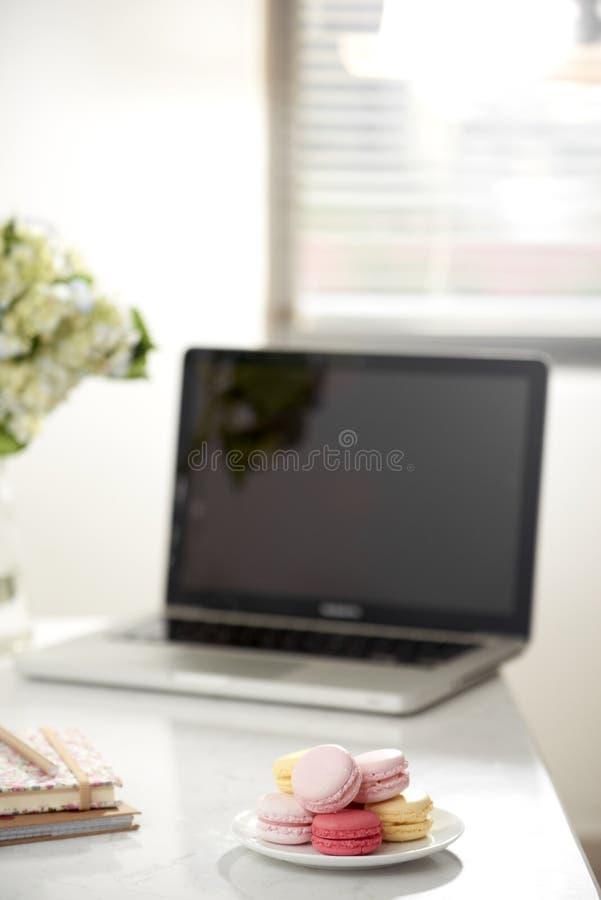 Bureau de siège social avec l'ordinateur portable d'écran vide, beau bouquet de hortensia, macaron dans l'avant près de la fenêtr image stock