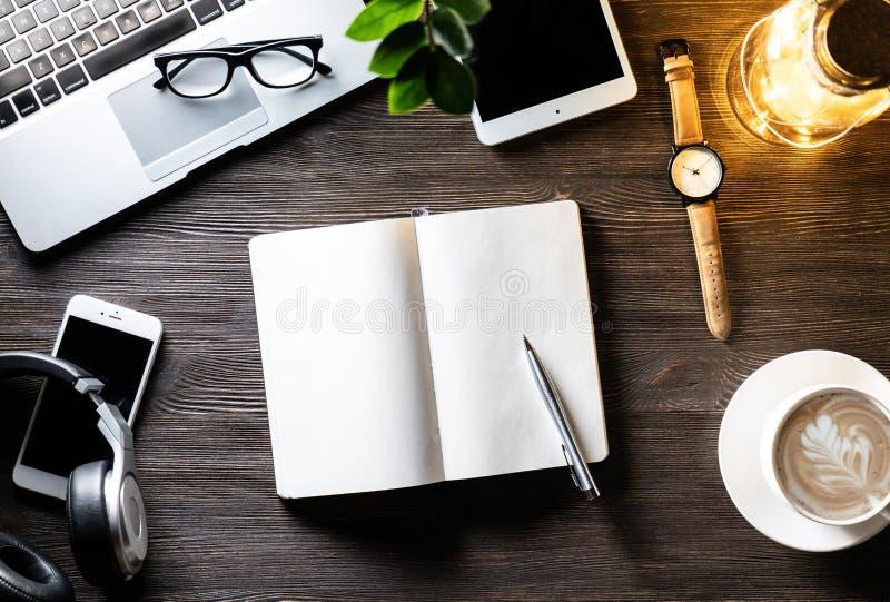 Bureau de travail d'affaires avec la lumière de lampe sur le lieu de travail en bois noir de table de dispositifs photographie stock libre de droits