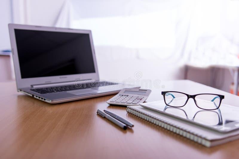 Bureau en bois avec l'ordinateur portable, stylos, verres images stock