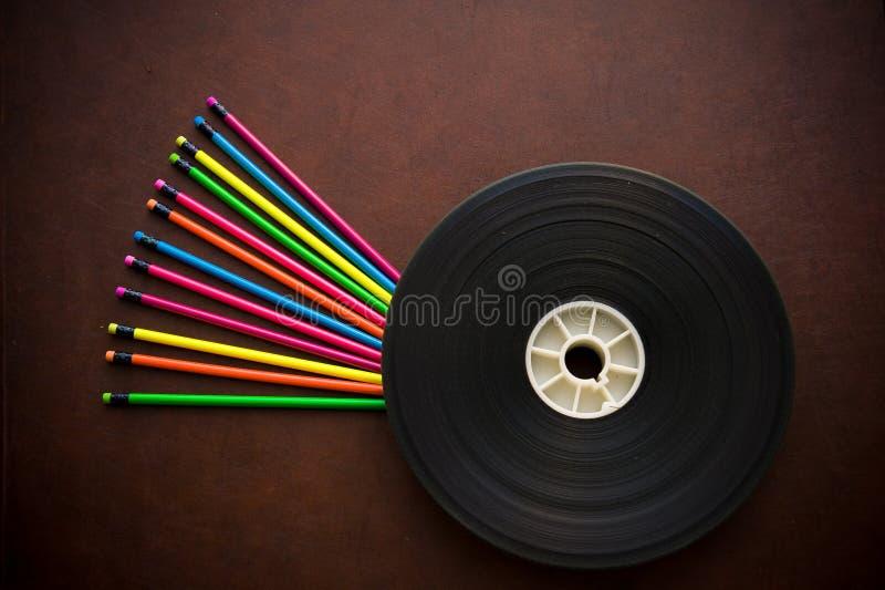 Bureau en bois avec la bobine colorée de crayon et de pellicule cinématographique photographie stock libre de droits