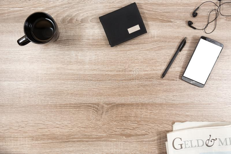 Bureau en bois avec le smartphone, écouteurs, stylo, portefeuille, tasse de café photo libre de droits