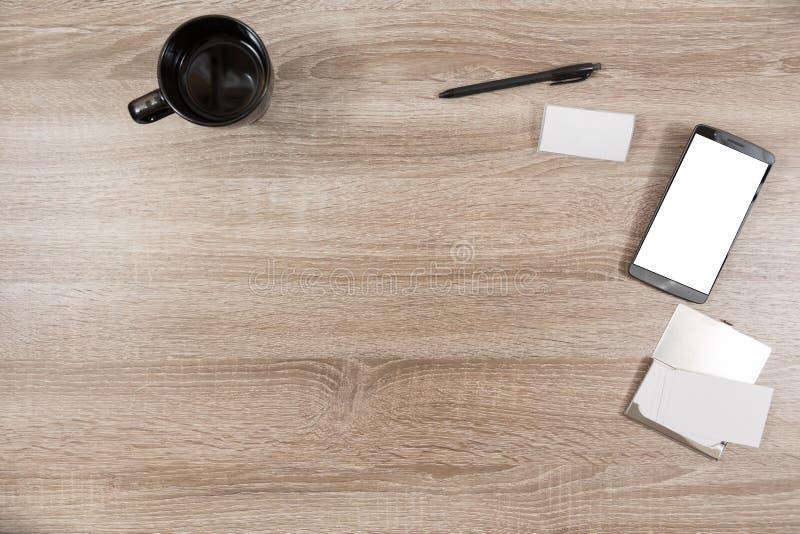 Bureau en bois avec le smartphone, étiquette de nom, cartes de visite professionnelle de visite dans un métal images stock