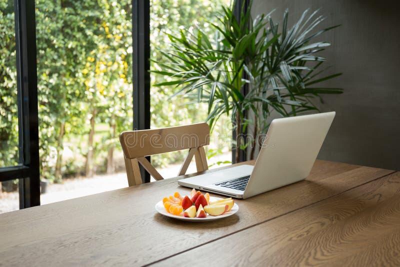 Bureau en bois avec les fruits frais et l'ordinateur portable avec la plante verte photos libres de droits
