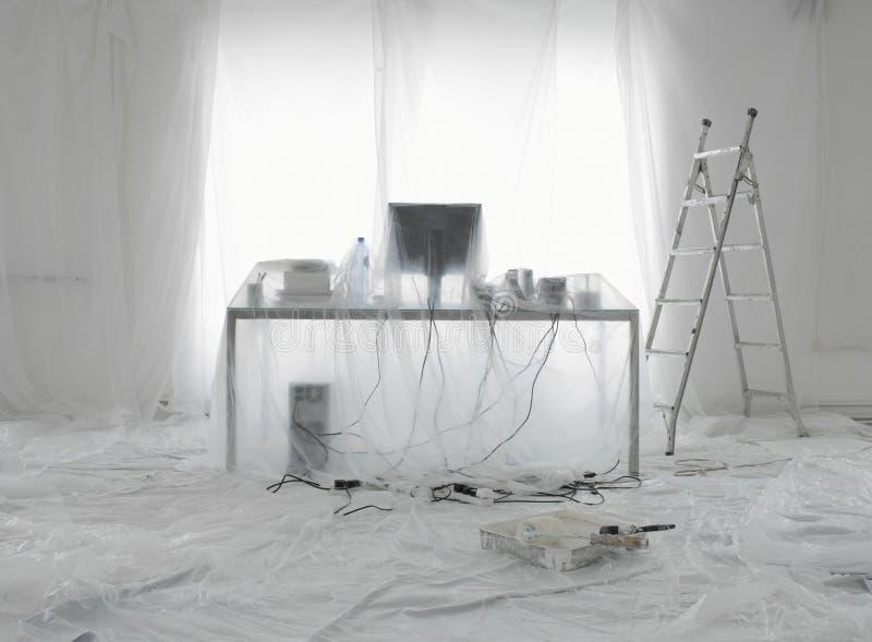 Bureau et ordinateur couverts en feuilles de poussière transparentes photographie stock