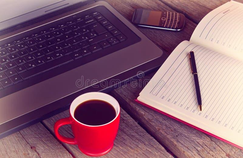Bureau fonctionnant avec la tasse du matin de vintage d'ordinateur portable et de téléphone portable d'ordre du jour de planifica images stock