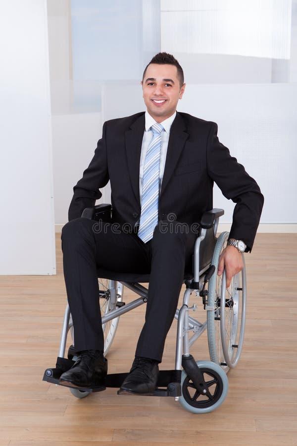 Bureau handicapé d'In Wheelchair At d'homme d'affaires photo stock