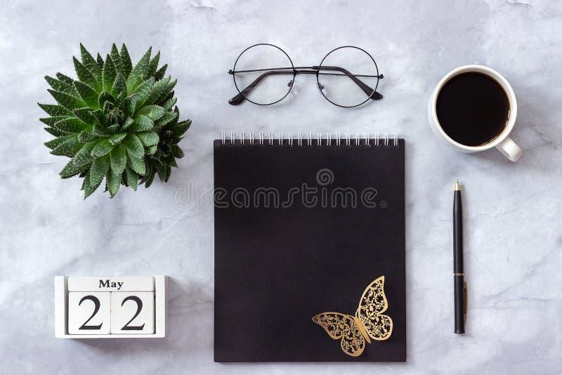 Bureau of huislijstbureau Houten kubussenkalender 22 Mei Zwarte blocnote, succulente kop van koffie, glazen op marmeren achtergro stock fotografie