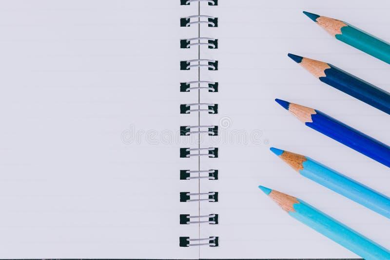 Bureau met blocnotes en gekleurde potloden met lege pagina's en copyspace stock fotografie