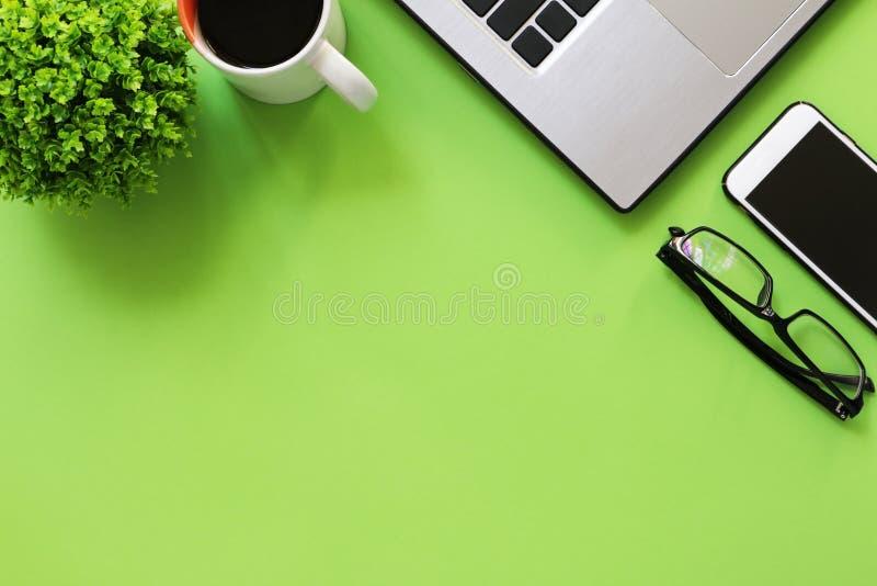Bureau met groene installatie, koffie, laptop smartphone en oogglazen stock afbeelding