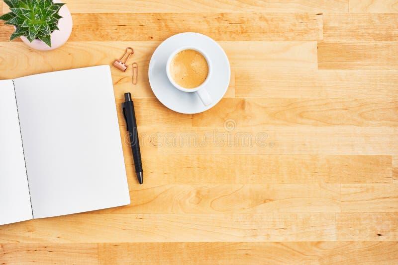 Bureau met lege notitieboekje, pen en kop van koffie stock afbeelding