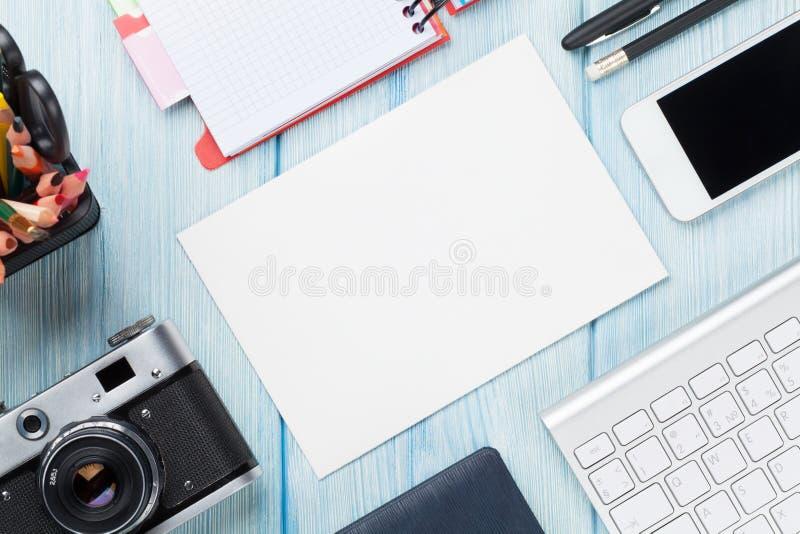 Bureau met levering, camera en lege kaart stock fotografie