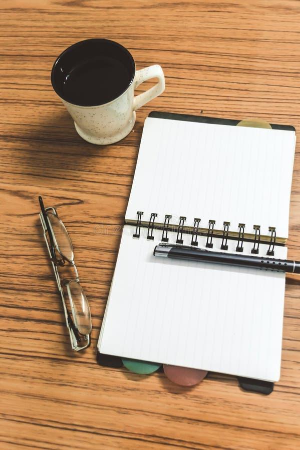 Bureau met open notitieboekje met blanco pagina's, oogglazen, pen en een kop van koffie Hoogste mening met exemplaarruimte Bedrij stock foto
