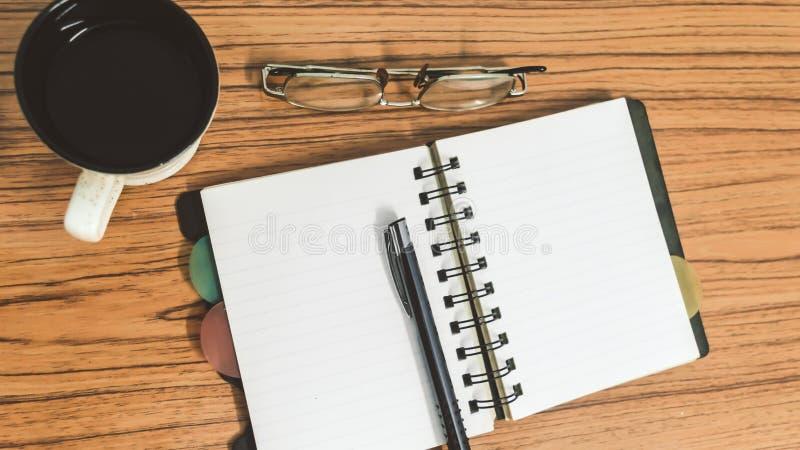 Bureau met open notitieboekje met blanco pagina's, oogglazen, pen en een kop van koffie Hoogste mening met exemplaarruimte Bedrij stock afbeelding