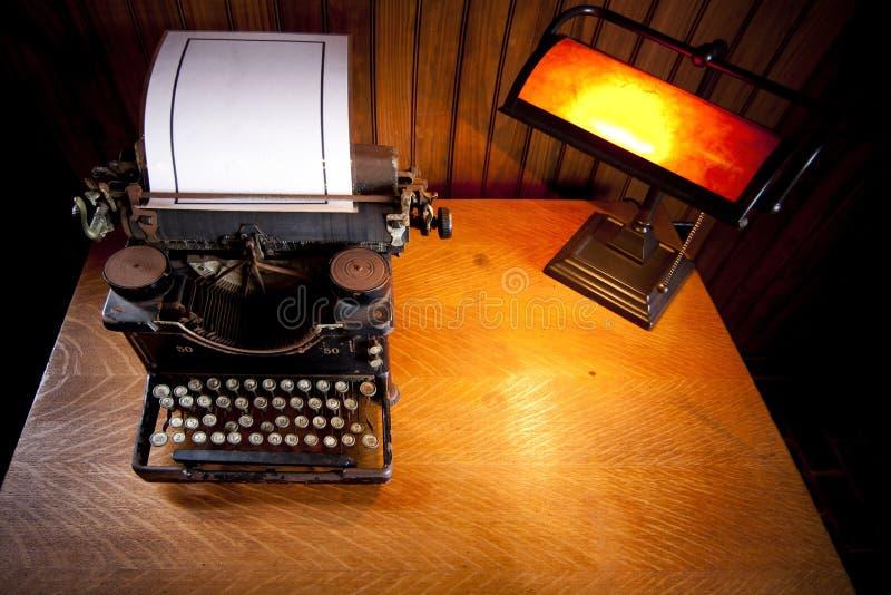 Bureau met oude schrijfmachine en lamp stock afbeeldingen