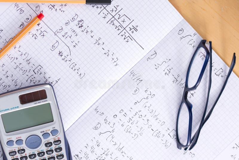 Bureau met van de de pennenwiskunde van calculatorglazen het thuiswerkoefenboek stock afbeeldingen