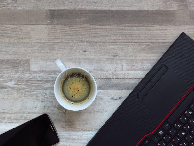 Bureau met zwarte laptop, gouden kleuren mobiele telefoon, een kop van koffie Zaken Succes Zoete croissant en een kop van koffie  royalty-vrije stock foto