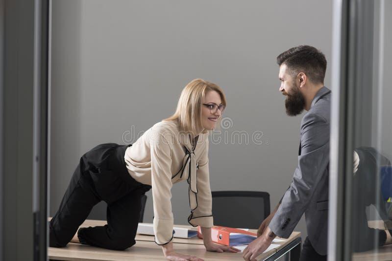 Bureau Romaans concept De sexy secretaresse verleidt werkgever in bureau De onderneemster op Desktop bekijkt gebaarde zakenman Me royalty-vrije stock afbeeldingen