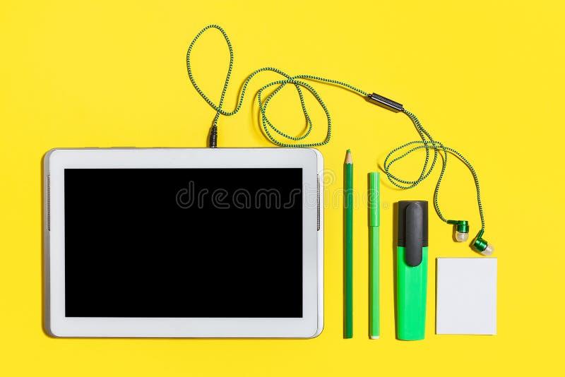 Bureau stationnaire et instruments sur une surface jaune image stock