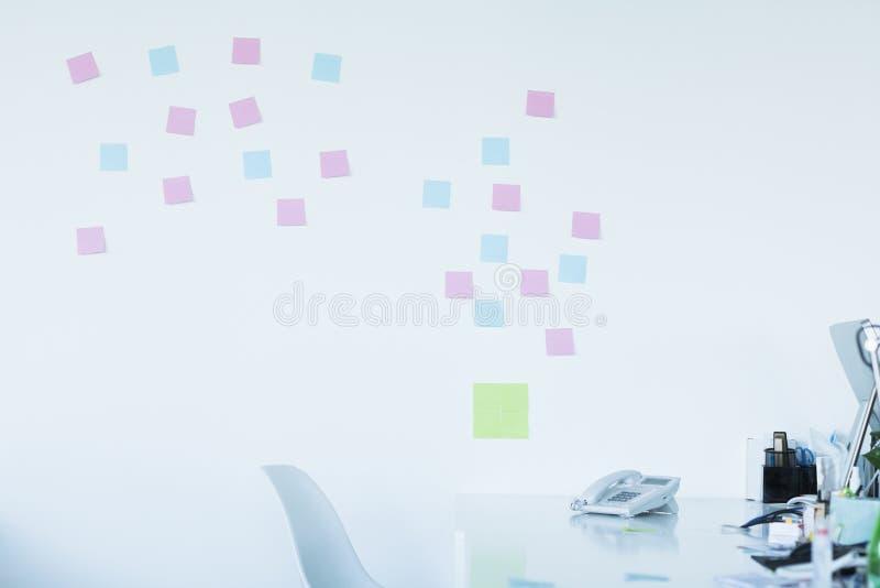 Bureau vide avec les notes adhésives colorées sur le mur photo libre de droits