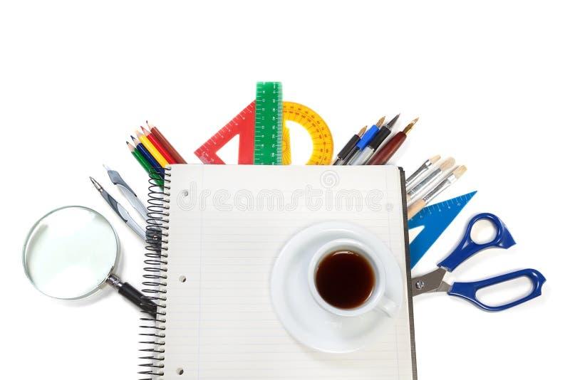 Bureauhulpmiddelen op het notitieboekje voor nota's en een kop van cof stock afbeeldingen