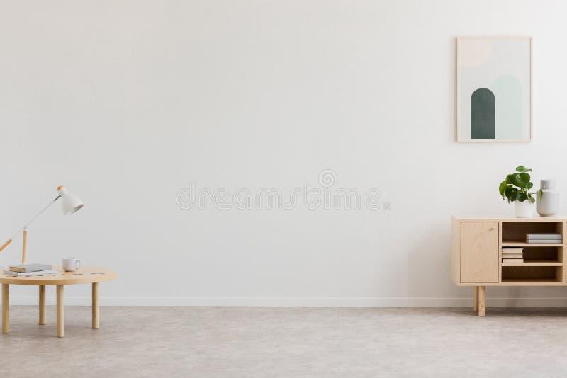 Bureaulamp op een kleine lijst en een eenvoudig, houten kabinet in een leeg woonkamerbinnenland met witte muur en plaats voor een stock afbeeldingen