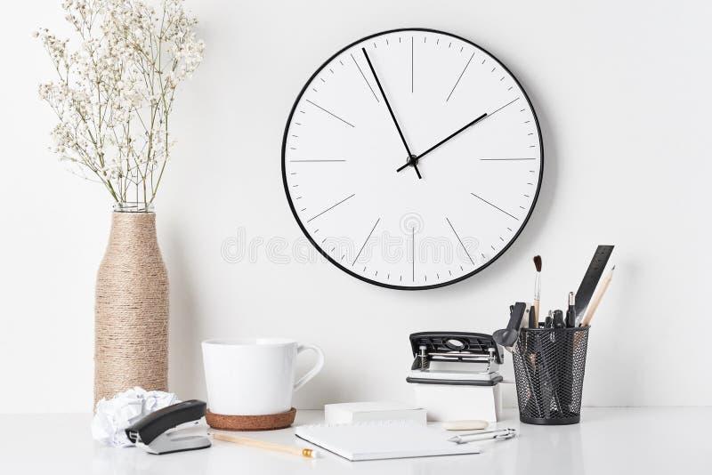 Bureaulevering en muurklok op wit stock afbeeldingen