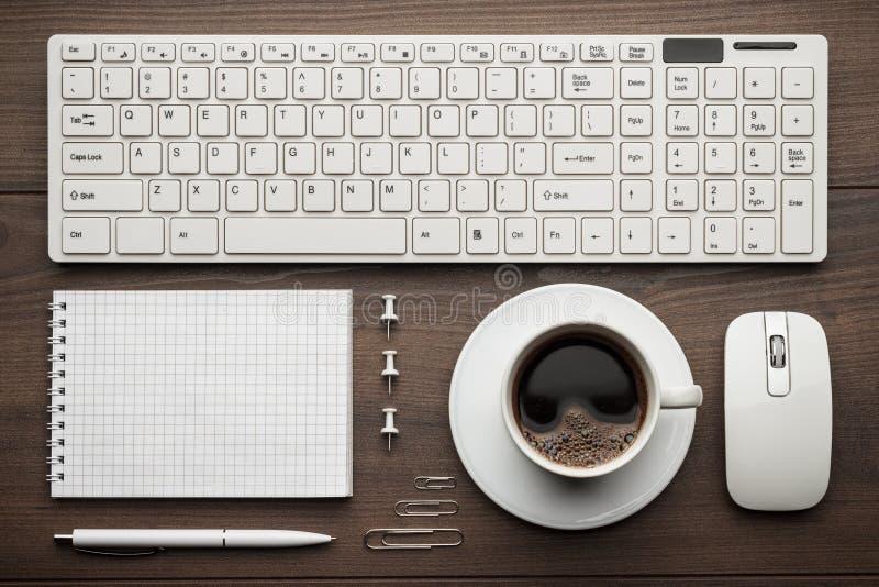 Bureaulijst met blocnote, computer en koffiekop stock foto's