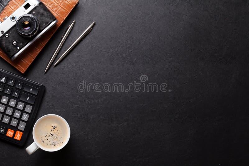 Bureaulijst met camera, levering en koffie stock afbeeldingen
