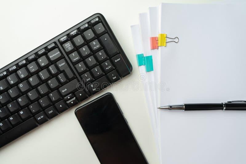 Bureaulijst met computertoetsenbord en levering Op witte achtergrond Hoogste mening met exemplaarruimte Spot omhoog royalty-vrije stock foto