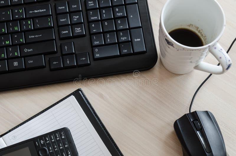 Bureaulijst met de muis en de koffie van het notitieboekjetoetsenbord royalty-vrije stock afbeelding