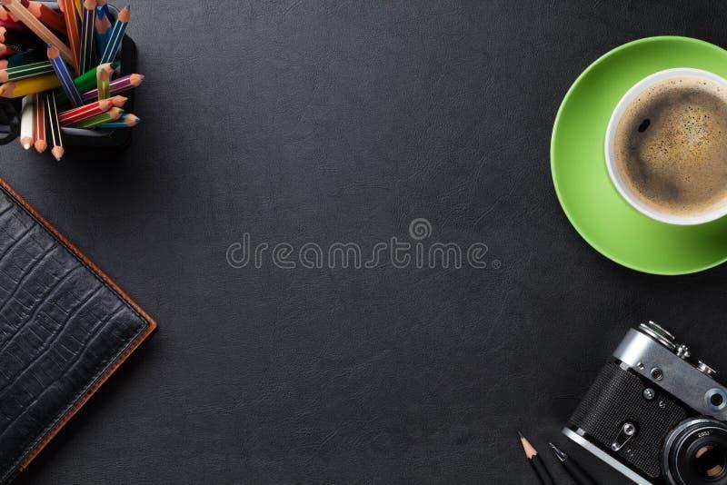 Bureaulijst met koffiekop, camera en levering stock afbeelding
