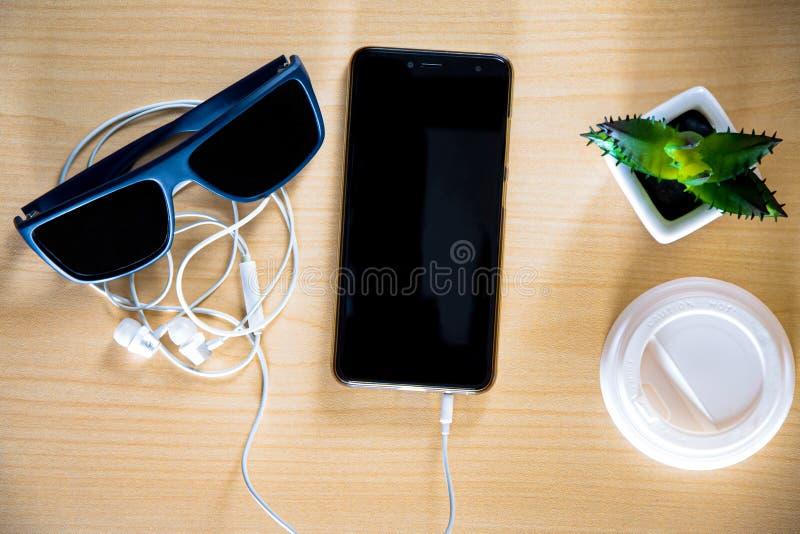 Bureaulijst Smartphone, hoofdtelefoons, koffie in een beschikbare kop, decoratieve cactus Houten lijst royalty-vrije stock foto's
