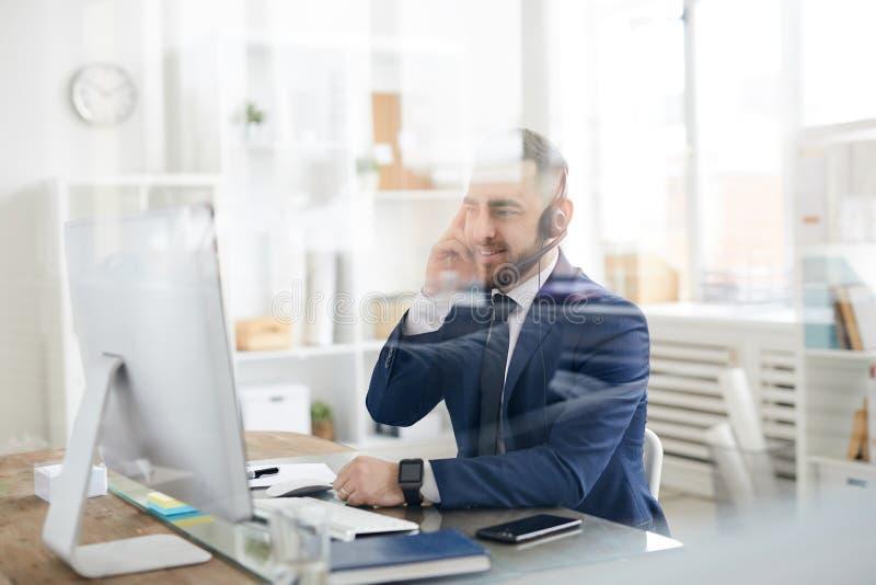 Bureaumanager met hoofdtelefoon stock afbeeldingen