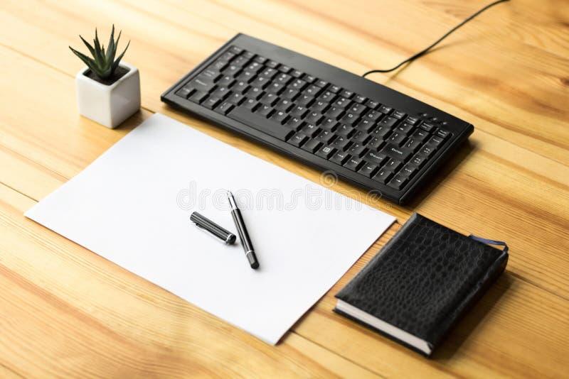 Bureaumateriaal met een notitieboekje, een blad van document, pen, toetsenbord op een houten lijst stock afbeeldingen