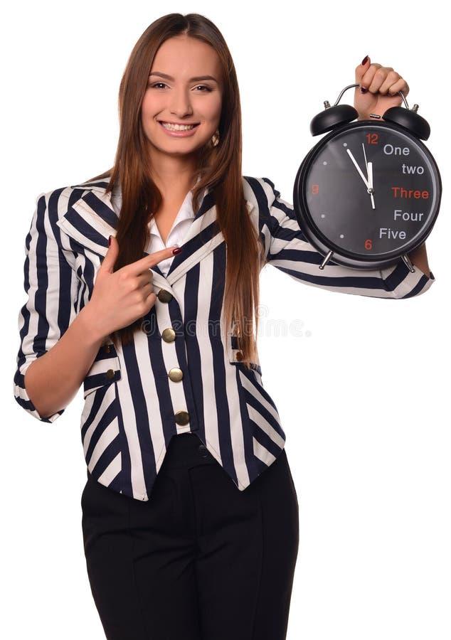 Bureaumeisje die die klok tonen op een witte achtergrond wordt geïsoleerd royalty-vrije stock foto