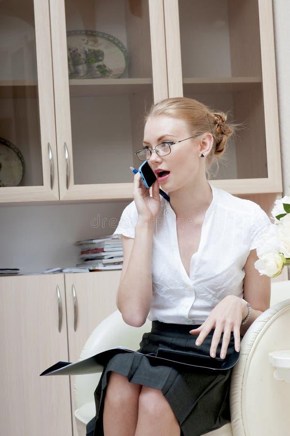 Bureaumeisje die op mobiele telefoon spreken stock foto