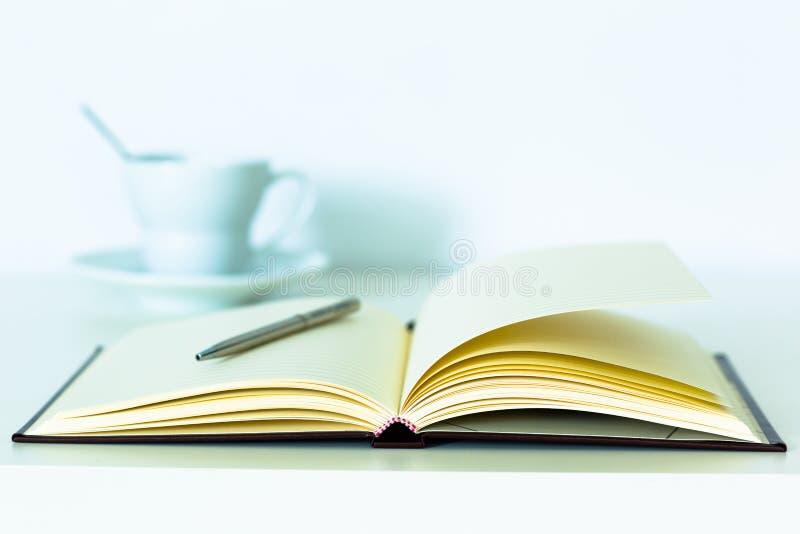 Bureaunotitieboekje en pen met koffiekop royalty-vrije stock afbeeldingen