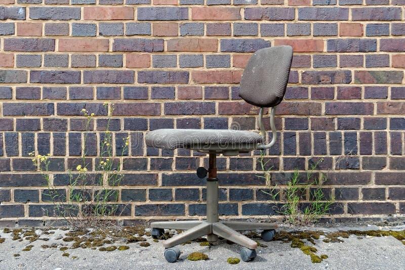 Bureaustoel voor bakstenen muur stock fotografie