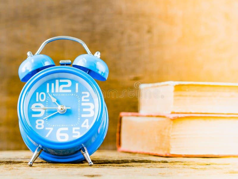 Bureautoebehoren met inbegrip van wekker en boeken op houten achtergrond royalty-vrije stock foto's