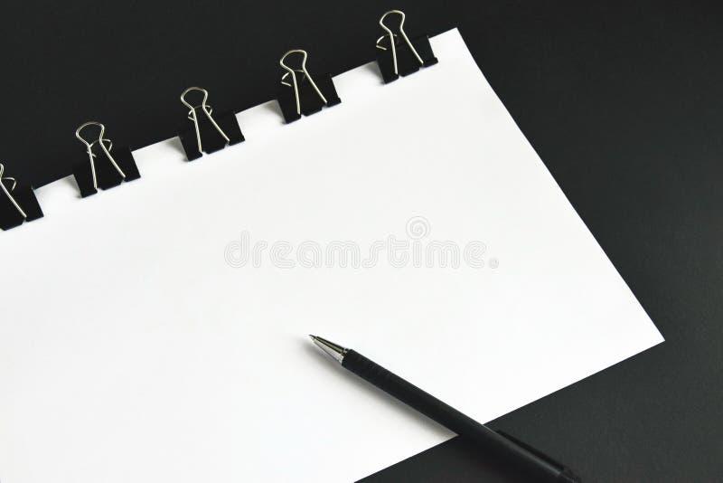 Bureautoebehoren, witte bladen, pen en bindmiddelenklem royalty-vrije stock afbeeldingen