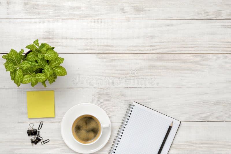 Bureauwerkplaats met groene houseplant, kop van koffie, open leeg notitieboekje en zwart potlood royalty-vrije stock foto