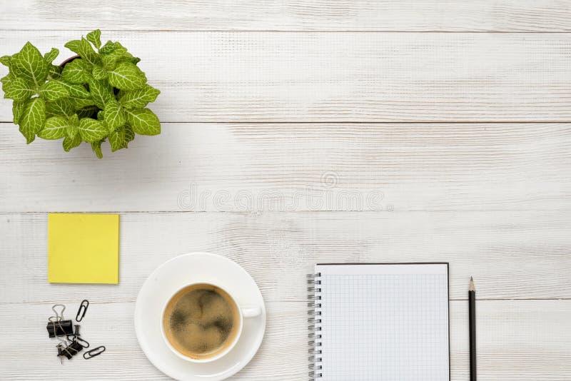 Bureauwerkplaats met groene houseplant, kop van koffie, open leeg notitieboekje en zwart potlood stock foto