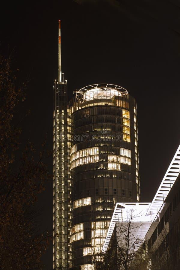 Bureauwolkenkrabber met antenne en helihaven bij nacht stock foto