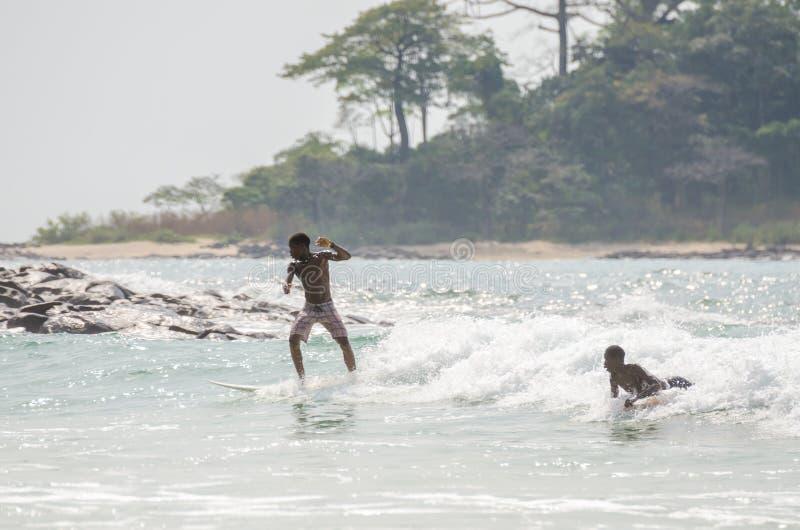Bureh plaża Sierra Leone, Styczeń, - 11, 2014: Dwa niezidentyfikowanej młodej Afrykańskiej chłopiec surfuje przy kipiel punktem w obraz royalty free
