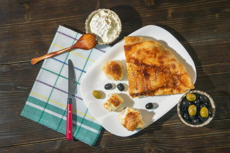 Bureks with cheese - national dish, popular in the Balkans. Kajmak in small dish. Flat lay. Dark rustic background stock photography