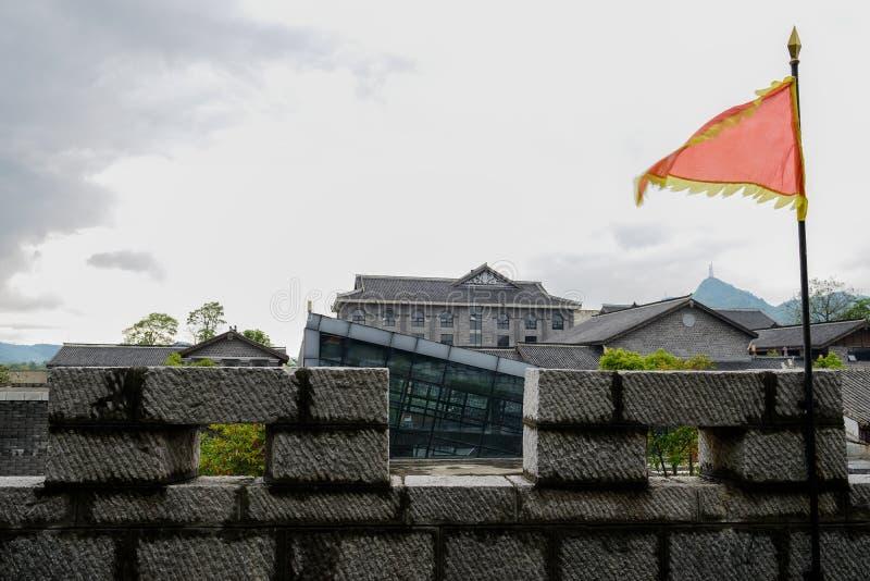 Burgartiges Geländer des Steins mit roter Fahne vor Fliese-überdachter Gestalt stockfotografie