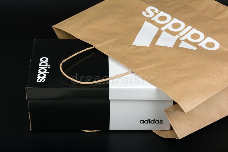BURGAS, BULGARIA - 8 MARZO 2019: Sacco di carta con la scatola originale di logo di Adidas e di scarpe di Adidas su fondo nero immagine stock