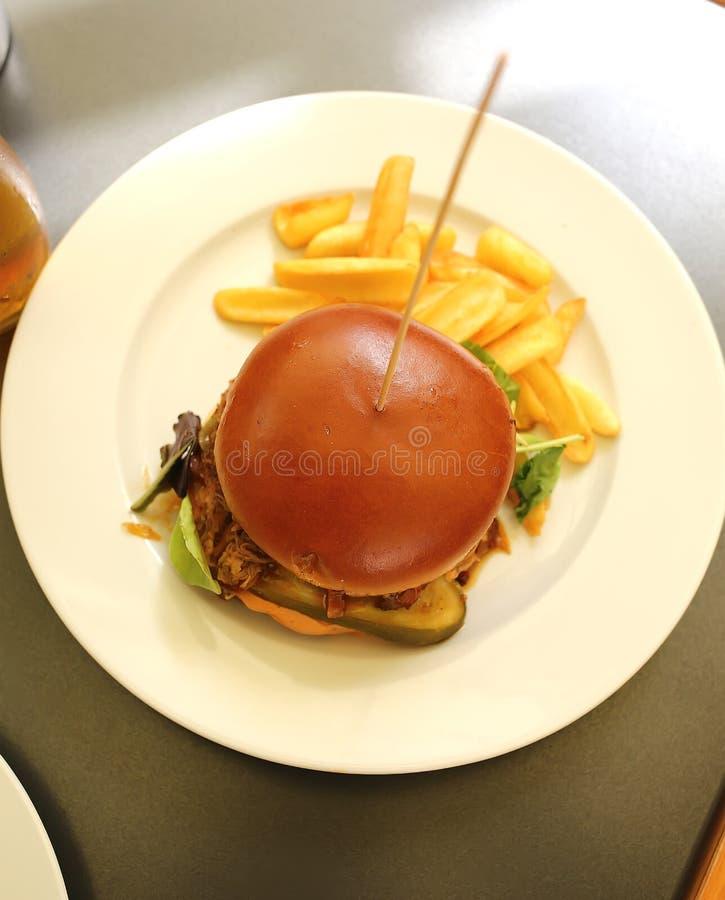Burger à la viande, au fromage et aux cornichons sur une assiette dans un restaurant de la rue images stock