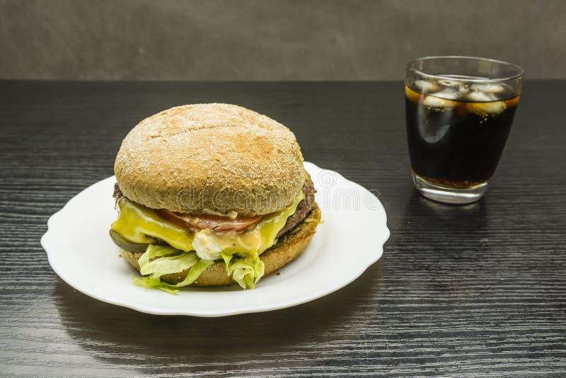 Burger βόειου κρέατος και ένα ποτήρι της κόλας με τον πάγο στοκ φωτογραφία