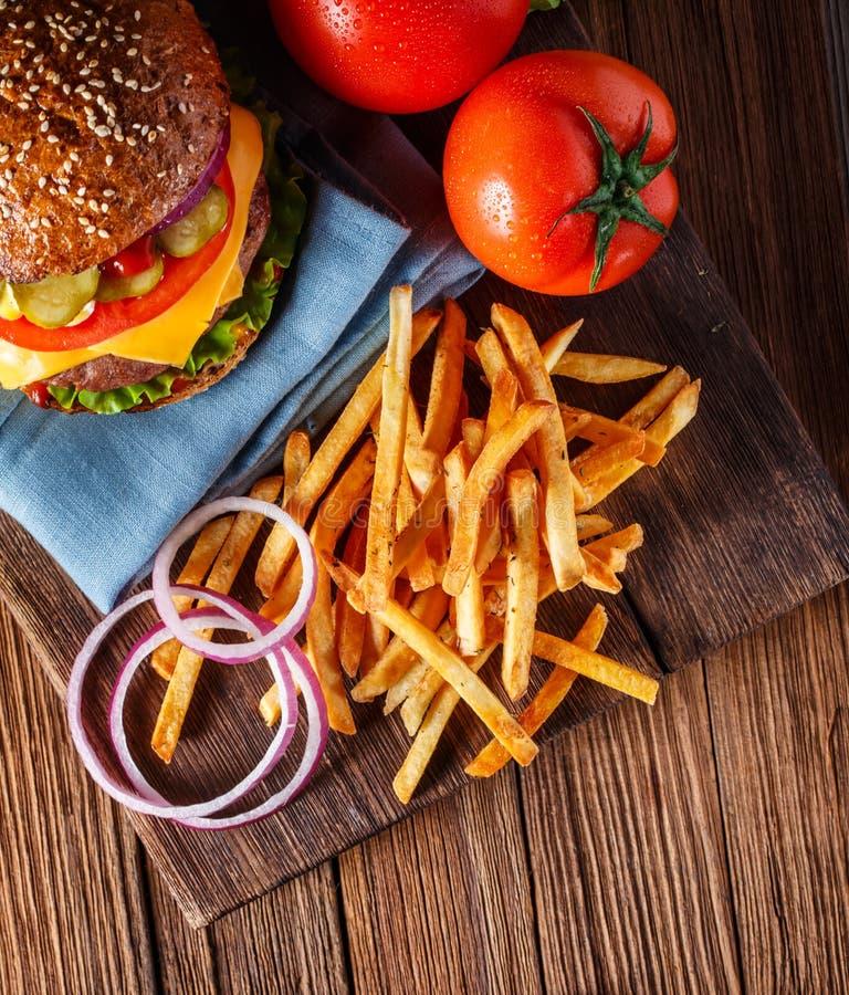 Burger και οι τηγανιτές πατάτες κλείνουν επάνω στο ξύλινο υπόβαθρο στοκ εικόνα με δικαίωμα ελεύθερης χρήσης